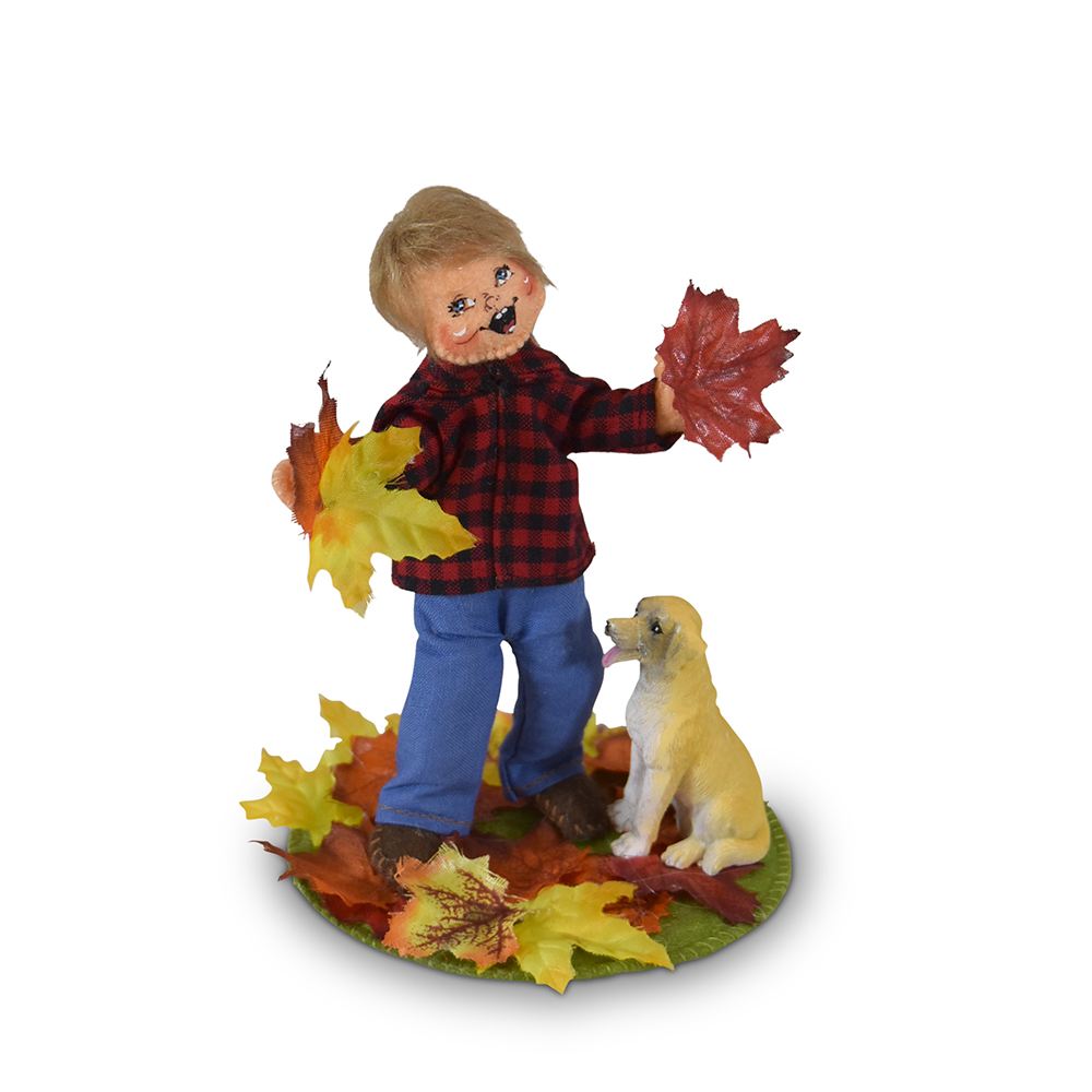 boy playing with dog in autumn leaves